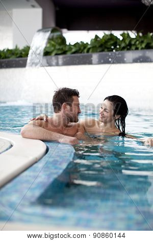 Couple relaxing in jacuzzi of spa center poster