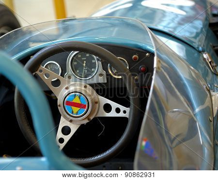 old sports car dashboard colored in silver and cyan
