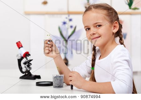 Young girl study plants in biology class - holding a seedling and test tube
