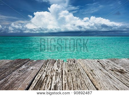 Crystal clear turquoise water and old wooden pier at tropical maldivian beach
