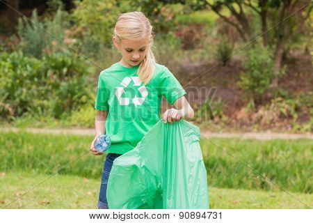 Happy little girl collecting rubbish on a sunny day