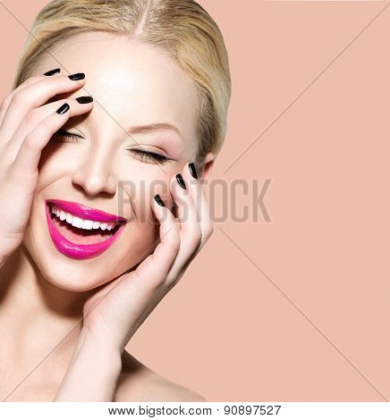 Laughing Beautiful Young Woman with Clean Fresh Skin close up over beige background. Beauty Portrait. Spa Woman Smiling and touching her skin. Perfect Fresh Skin. Model. Youth and Skin Care Concept