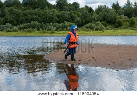 Little Boy In A Lifejacket Running On Sandbar