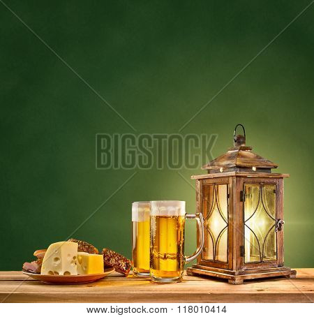 old lantern with beer and cheese on green vintage background