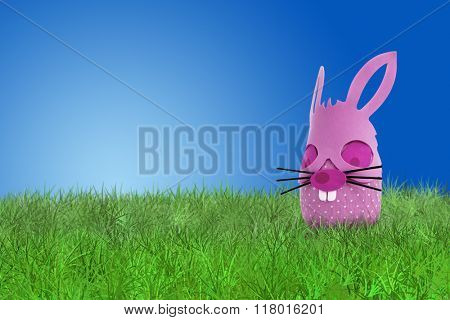 Funny pink Easter bunny on grass on blue background