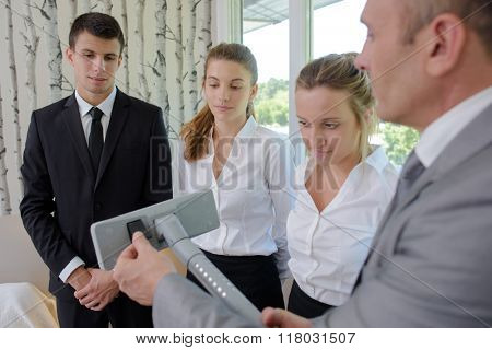Man explaining controls of vacuum cleaner to students