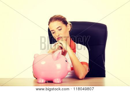 Female doctor  sitting behind the desk and holding a piggybank