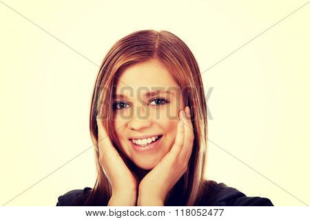 Teenage happy woman holding both hands on cheeks