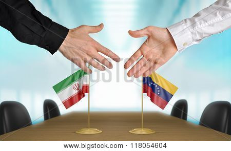Iran and Venezuela diplomats shaking hands to agree deal