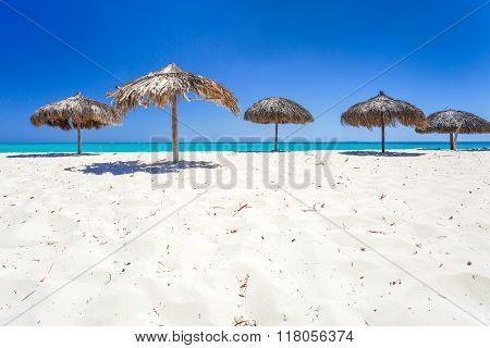 Beach Umbrellas made of palm leafs on exotic beach