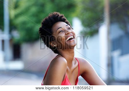 Young African Woman Sitting Outdoors And Laughing