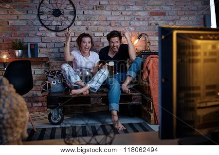 Excited couple watching tv at home, jittering.
