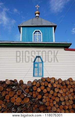 Woodpile at christian church building Pevek town Chukotka Russia poster