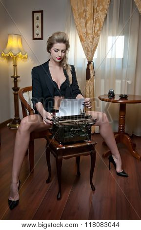 Attractive sexy blonde woman with black bra posing provocatively sitting on chair typing