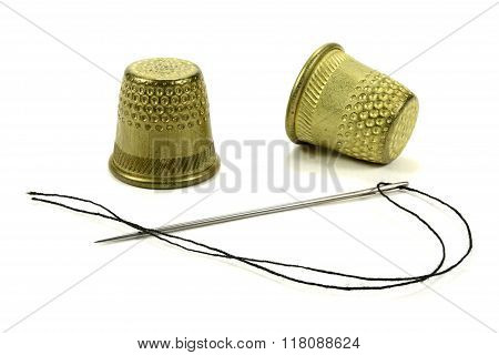 Old Brass Thimbles And Thread With A Needle For Sewing On A White Background