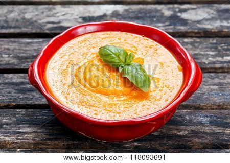 Carrot cream soup on wooden background.
