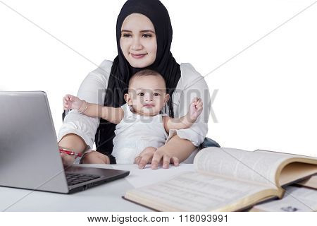 Busy Mother Using Laptop With Her Baby