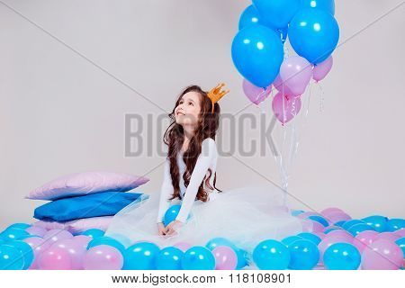 Cute little princess girl sitting among balloons in room over white background. Looking at camera