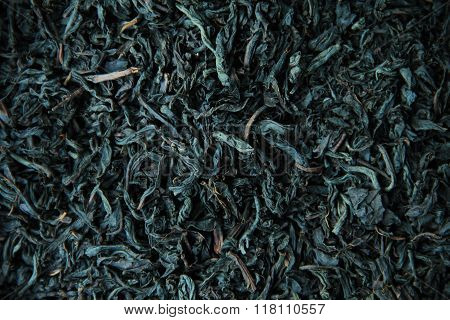 Black tea background with dry leaves close up