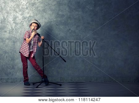 Little boy singing with microphone on a grey wall background