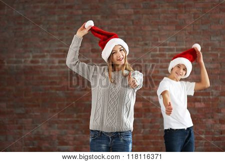 Happy cousins have fun on brick wall background