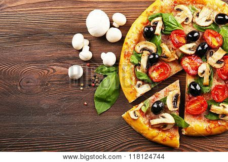 Sliced delicious tasty pizza with vegetables on wooden table