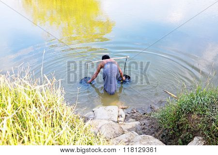 Water carrier with two buckets getting water in the countryside from Myanmar