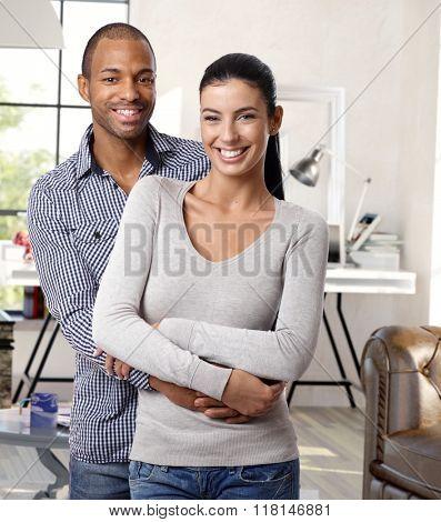Happy young interracial loving couple hugging and smiling at home, looking at camera.