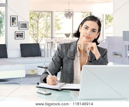Portrait of elegant smart caucasian businesswoman at home desk, wearing suit, sitting in front of laptop computer, personal business organizer. Hand under chin, looking at camera, smiling.