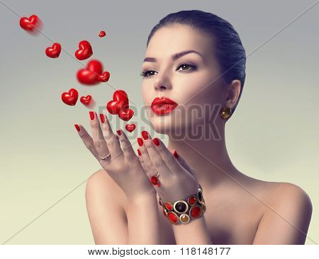 Beauty Woman with perfect make up Blowing Valentine hearts. Valentine's Day Beautiful Fashion sexy Girl showing copy space on the open hand. Gestures for advertisement