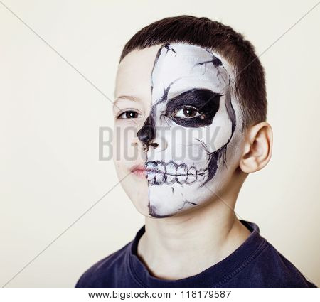 little cute boy with facepaint like skeleton to celebrate halloween