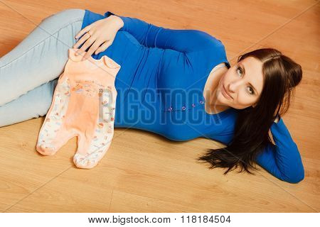 Pregnant Woman With Clothes For Unborn Baby