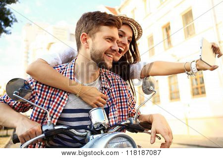 Happy couple on scooter making selfie photo on smartphone