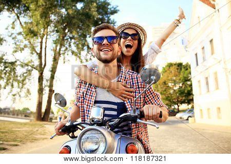 Couple in love riding a motorbike , Handsome guy and young sexy woman travel . Young riders  enjoying themselves on trip. Adventure and vacations concept. poster