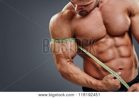 Closeup Muscular bodybuilder measuring biceps with tape measure isolated over gray background. Bodybuilder tries to measure gain in bicep by himself. poster