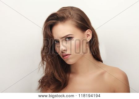 Closeup portrait of grumpy young cute playful brunette woman posing with bare shoulders against whit
