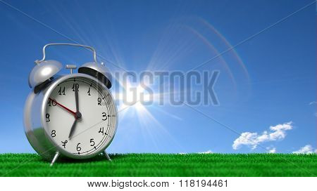 Retro alarm clock closeup on grass with blue sky and sun shining.