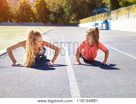 Mother And Little Daughter Are Doing Exercise In The Stadium
