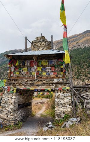 Colorful ornate buddhist stupa. Traditional village entrance in Nepal.