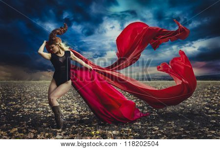 blonde girl with a huge red cloth in the wind, warrior and freedom