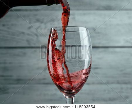 Pouring red wine into the glass against grey wooden background