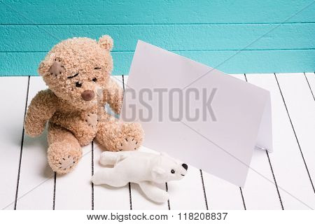 Two teddy bear sitting on white wooden floor in blue-green background with blank note