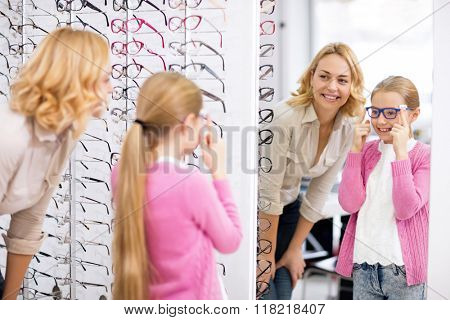 Young girl look herself in the mirror with new eyeglasses in optical
