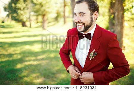 Stylish groom in tuxedo laughs suit marsala red, burgundy bow tie. Man buttoning his jacket outdoors