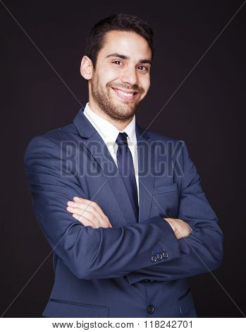 Young happy smiling business man on black background