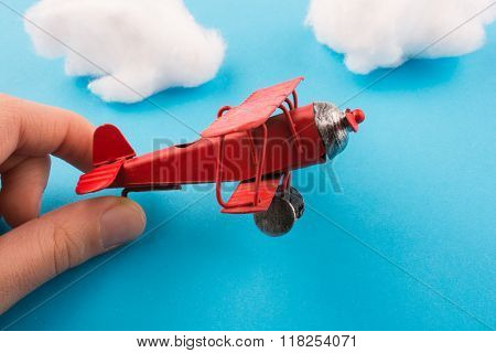 Toy Airplane In Hand And Clouds