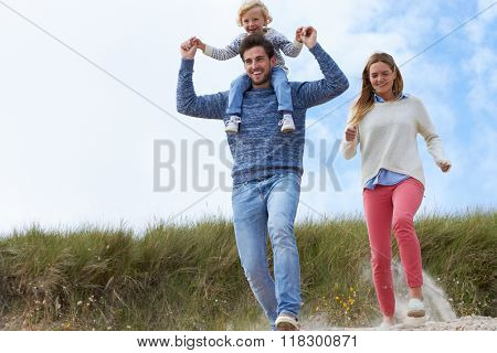 Family On Beach Vacation Running Through Dunes