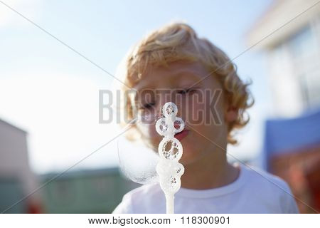Close Up Of Young Boy Blowing Bubbles