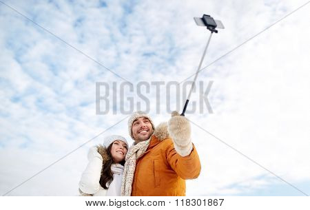 people, season, love, technology and leisure concept - happy couple taking picture with smartphone selfie stick on over winter background