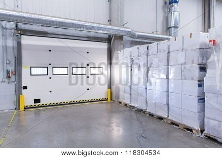 logistic, storage, shipment, industry and manufacturing concept - warehouse door or gate and cargo boxes